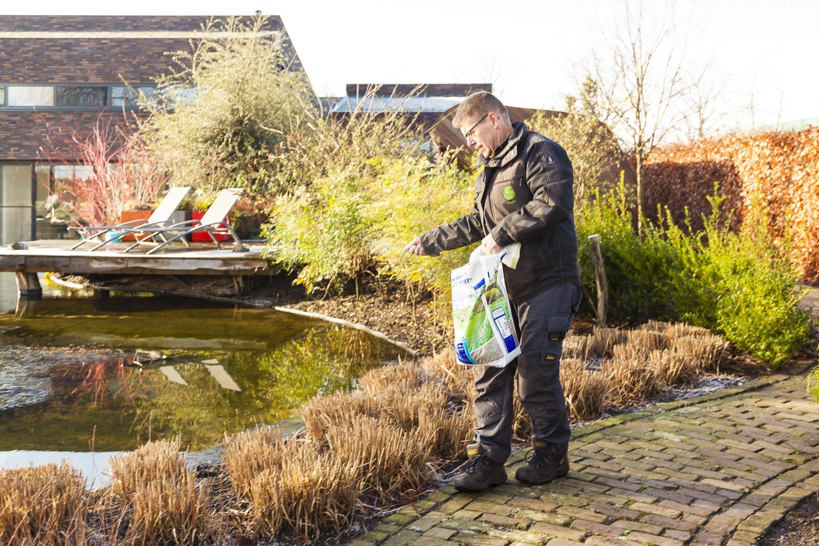 Gert-Jan Schonenberg is kalk aan het strooien in de tuin