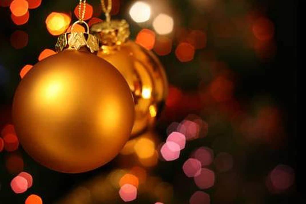 Gouden kerstballen hangend in een kerstboom